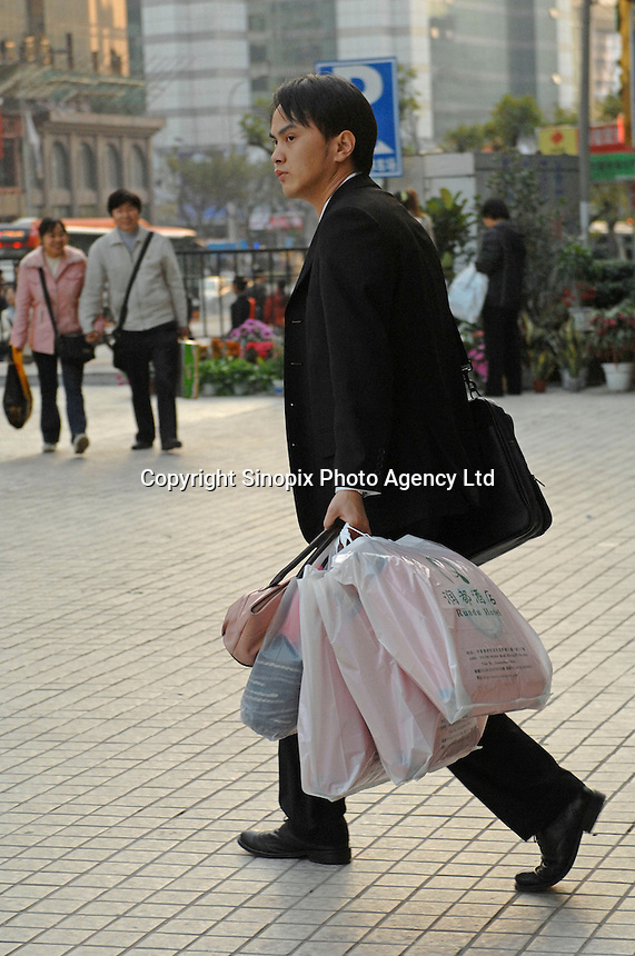 Shoppers clutch onto sales bags at pre-Chinese New Year sales in Tien He, Guangzhou, China. The Chinese consumer is inreasingly seen as an important engine  in the world economy..29 Jan 2007