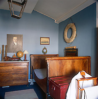 A blue bedroom furnished in a traditinal way wtih a single sleigh bed and a chest of drawers.