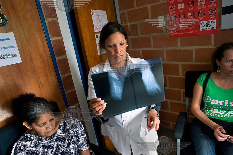 A Cuban medical worker examines an X-ray of a patient at a health clinic, part the Mission Barrio Adentro project. This aims to offer poor Venezuelans access to health and medical facilities and is funded from oil revenues. The project employs 30, 000 Cuban health professionals: doctors, dentists, physiotherapists and technicians etc.