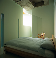 A Japanese-style bed in a small guest bedroom with part of the original factory floor above it