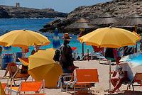 Lampedusa / Italia.Un immigrato vende borse e cappelli ai turisti in vacanza..Foto Livio Senigalliesi