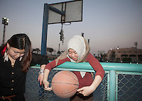 Egypt / Cairo / 9.3.2013 / Fatma, 22, Muslim (Huizu) from Henan talks with her friend (Hanzu, non Muslim) in a basketball court after they played, in a sport center nearby the airport in Cairo. © Giulia Marchi / Anzenberger