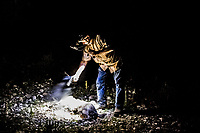 Hunting guide, Larry Hromadka, fires his pistol to end the suffering of the animal as he stands above a hog shot by Daniel Schaan, 15, unseen, during a night boar hunt at the Ox Ranch on 17th of August, 2017 in Uvalde, Texas, USA. <br /> Photo Daniel Berehulak for the New York Times