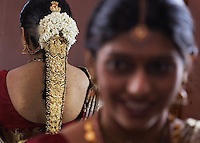 This is an arranged marriage between two coffee plantation owner families 5 hours from Bangalore in Chikmagalur, India.  The girls family approached the wealthier coffee plantation family and was accepted.  She is wearing the wedding jewelry of her extended family.  The piece in her hair is 2KG and over 100 years old.  The workmanship places its value at around $500,000 USD.  Total wealth hanging off this bride is about $700,000.  There were times when it was painful for her to keep her head straight...We drove to Chikmagalur and first met up with the bride Nagavika C.R. at her house. On that day, we also met her father Mr. Ravi Shankar, sisters Kavya and Supreetha. Her cousin Shilpa Kiran was the one who was explaining about the jewellery to us...We also drove up to meet the groom Vignesh Gowda.