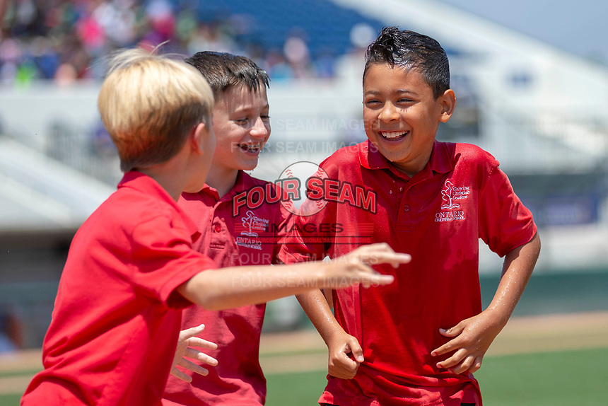 Young Rancho Cucamonga Quakes fans from Ontario Christian School share a laugh after getting soaked by Aftershock between innings of the game against the Visalia Rawhide at LoanMart Field on May 14, 2018 in Rancho Cucamonga, California. The Rawhide defeated the Quakes 5-0.  (Donn Parris/Four Seam Images)