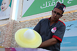 A Palestinian man makes coloured cotton candy in a park in Gaza city on August 18, 2019. Fayiz al-Wakeel, or 'the smile maker', developed his own candy floss machin to work by battery power to help him moving between vital districts in the Gaza city and make cotton candy with lovely shapes. Photo by Mahmoud Ajjour