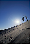 Two young men jumping off sand dune ridge; Umpqua Dunes, Oregon Dunes National Recreation Area, Oregon coast.