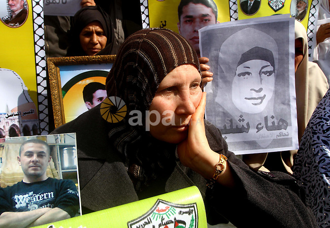 "Palestinians demonstrate in solidarity with  Hana'a Shalabi during a protest in Gaza City, on mar. 05, 2012. Shalabi, released by Israel in a prisoner swap last year but re-arrested earlier this month and held without charge, is on a hunger strike to protest her treatment, officials said. The Arabic writing on the sign reads ''Down with administrative detentions"". Photo by Ashraf Amra"