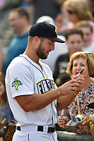 Designated hitter Tim Tebow (15) of the Columbia Fireflies signs autographs before a game against the Lexington Legends on Saturday, April 22, 2017, at Spirit Communications Park in Columbia, South Carolina. Lexington won, 4-0. (Tom Priddy/Four Seam Images)