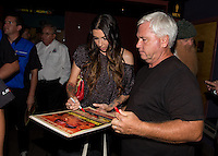 Aug. 29, 2013; Avon, IN, USA: NHRA funny car driver Alexis DeJoria signs autographs for fans during the premiere of Snake & Mongoo$e at the Regal Shiloh Crossing Stadium 18. Mandatory Credit: Mark J. Rebilas-