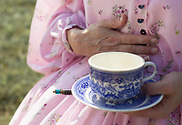 NWA Democrat-Gazette/CHARLIE KAIJO Joli Lewis of Joplin, Mo. holds a hat pin and tea cup, Friday, October 4, 2019 at a field north of Pea Ridge along the Missouri border in Pea Ridge. Lewis is a seamstress who created her entire outfit by hand including her corset, cage and two starch petty coats. <br /> <br /> Members of the Trans Mississippi Brigade set up camp for visitors to see life as it was in the 1860s in a battle camp. The camp will be open from 9 a.m. to 9 p.m. Friday through Sunday. There will be two battle reenactments — one at 1 p.m. Saturday and the other at 1 p.m. Sunday. The battle on Saturday will reenact the Battle of Elkhorn that was won by the Confederates. The battle on Sunday will be Welfley's Knoll and the Union will win.