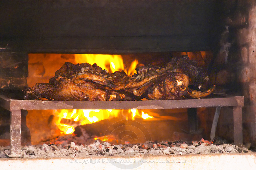 Meat on the grill being barbecued: lamb and pork over the char coal charcoal in front of the fire. Bodega Pisano Winery, Progreso, Uruguay, South America