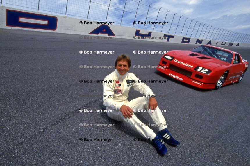DAYTONA BEACH, FL - FEBRUARY 13: Derek Bell of Great Britain sits on the Turn 4 banking in front of a Chevrolet Camaro Z28 before the IROC International Race of Champions race at the Daytona International Speedway in Daytona Beach, Florida, on February 13, 1987.