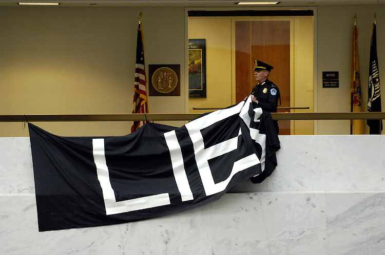 Protesters are removed from the 5th floor of the Hart Senate Office Building by U.S. Capitol Hill Police after they hung anti-war banners from the hand rails in the upper floor atrium. Here a U.S. Capitol Hill Policemen removes one of the anti-war banners that was hung from the hand rails in the upper floor atrium.