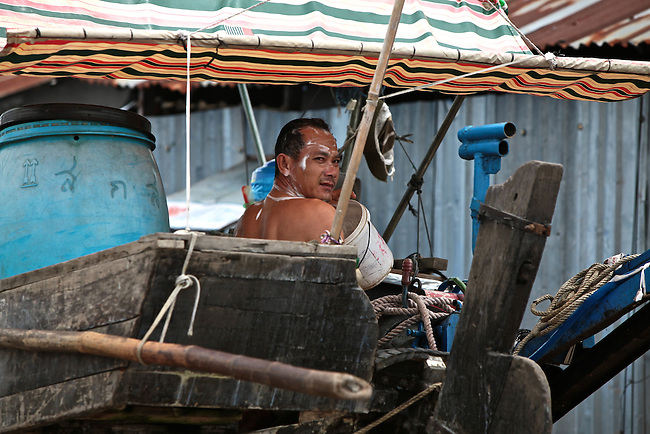 A man bathes on the back of a junk on the Hau River in the Mekong Delta, south of Can Tho, Vietnam. Sept. 30, 2011.