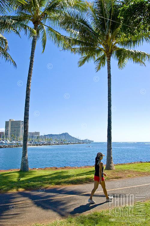 A woman walks the curving path through Aina Moana Park near Waikiki.  Diamond Head is in the background.