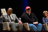January 12, 2012  (Washington, DC)  Radio and television talk show host Tavis Smiley (left) introduces author and movie producer Michael Moore during a panel discussion on restoring America's prosperity at the George Washington University Lisner Auditorium in Washington. (C-R)  Michael Moore, Suze Orman.  (Photo by Don Baxter/Media Images International)