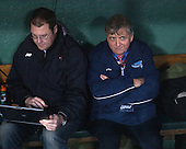 Joe Bertagna sits in the visitors' dugout with the Red Sox's weather tracker. - The University of Maine Black Bears defeated the Boston University Terriers 7-3 (2EN) on Saturday, January 11, 2014, at Fenway Park in Boston, Massachusetts.