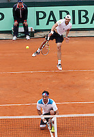 Italy's Simone Bolelli serve behind Fabio Fognini during  Davis Cup quarter-final doubles tennis match against Britain's Andy Murray and Ross Hutchins   in Naples April 5, 2014.