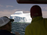 Toursits watching an iceberg floating in the bay at St Anthony, Newfoundland and Labrador, Canada
