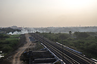 Smoke rises next to a train line in Waragal, Telangana, Indiia, on Sunday, February 10, 2019. Photographer: Suzanne Lee for Safe Water Network