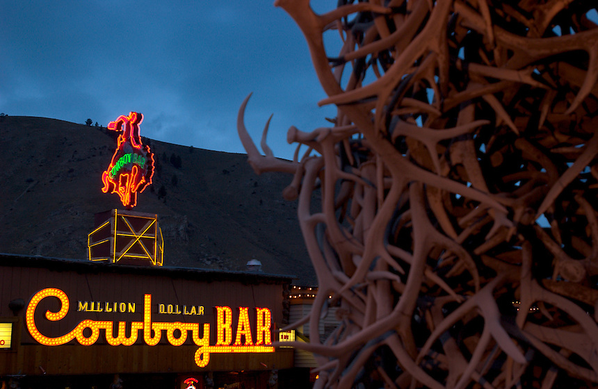 The lights of the Million Dollar Cowboy Bar stand behind one of four elk antler arches on the town square in Jackson, Wyo. (Kevin Moloney for the New York Times)