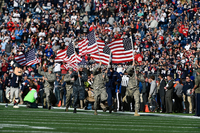 November 23, 2014 - Foxborough, Massachusetts, U.S.- Members of the armed forces run onto the field carrying American Flags before the NFL game between the Detroit Lions and the New England Patriots held at Gillette Stadium in Foxborough Massachusetts. The Patriots defeated the Lions 34-9. Eric Canha/CSM