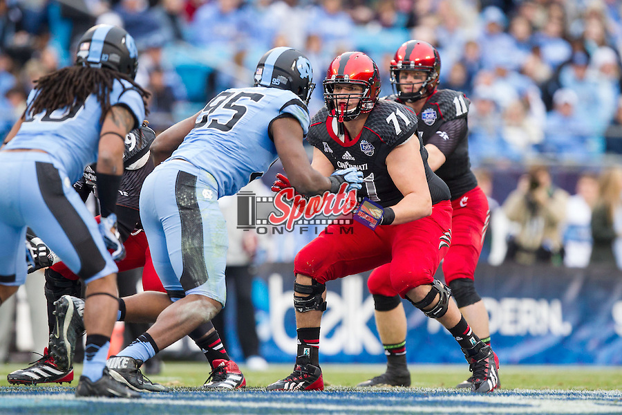 Eric Lefeld (71) of the Cincinnati Bearcats prepares to block Kareem Martin (95) of the North Carolina Tar Heels during the Belk Bowl at Bank of America Stadium on December 28, 2013 in Charlotte, North Carolina.  The Tar Heels defeated the Bearcats 39-17.   (Brian Westerholt/Sports On Film)