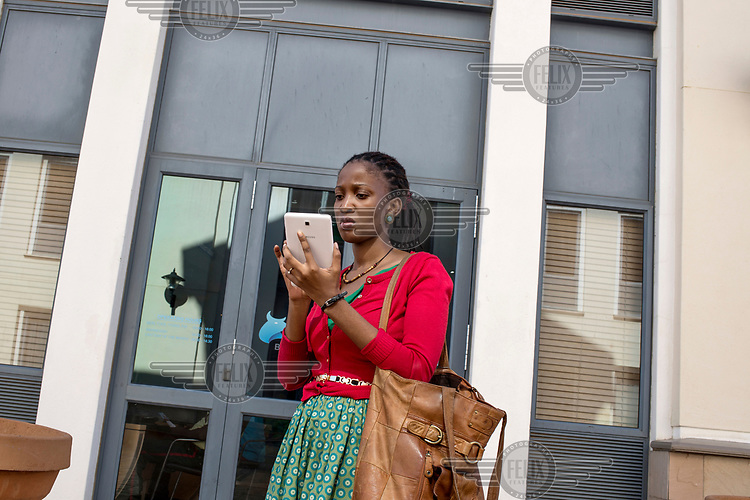 A woman working for GIZ, a German services provider, using a phablet outside the company's offices.
