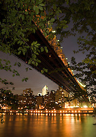 AVAILABLE FROM JEFF AS A FINE ART PRINT.<br /> <br /> AVAILABLE FROM CORBIS FOR COMMERCIAL AND EDITORIAL LICENSING. Please go to www.corbis.com and search for image # 42-23796549.<br /> <br /> Queensboro Bridge, East River and Midtown Manhattan Skyline at Night, Viewed thru Trees on Roosevelt Island, New York City, New York State, USA