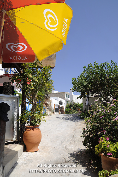 Typical narrow street of Chora Sfakion with Algida umbrella and green bushes