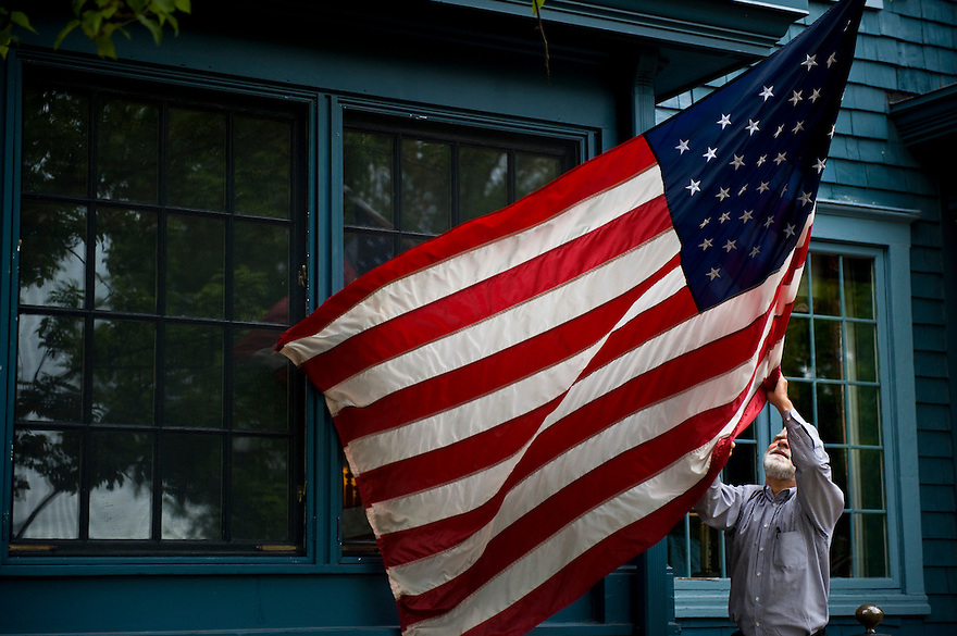 Sherwood Inn General Manager Michael Tutor unwraps and straightens the American flag hanging in front of the popular local establishment. Throughout the village American flags hang from the front of several houses along the streets...