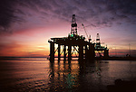 Two Oil drilling rig in Elliot Bay at sunset moored at the Port of Seattle for repairs, Seattle, Washington State USA