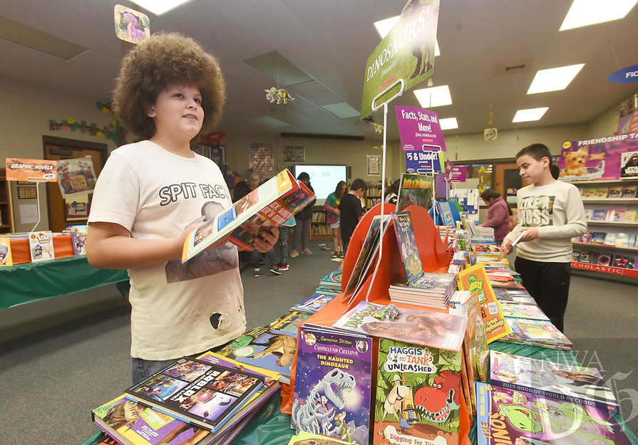 NWA Democrat-Gazette/FLIP PUTTHOFF <br /> BOOK FAIR FUNDRAISER<br /> Issac Cunningham (cq) (left), a fifth-grade student at Bonnie Grimes Elementary in Rogers, shops Wednesday Feb. 6 2019 at the school's book fair. Students select from an array of books and posters and purchase them as a fundraiser for the school library, said Linda Jefferson, librarian at Grimes. The book fair continues through Friday. Several schools in the Rogers district hold book fairs in February, Jefferson added.