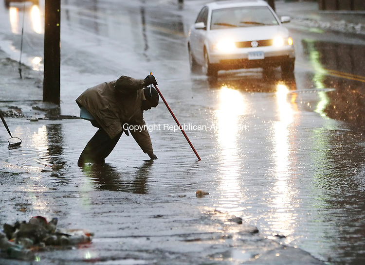WATERBURY, CT 02/01/08- 020108BZ02- Ray Simmons, of Waterbury, tries to clear a drain on East Farm Street to alleviate flooding in front of E&amp;J's Cafe Friday.<br /> Jamison C. Bazinet Republican-American