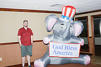 "Photographer M. Scott Brauer poses next to an inflatable elephant holding a sign reading ""God Bless America"" in a hallway outside the Palm Beach Republican Club and West Palm Beach Victory Headquarters office in West Palm Beach, Florida. The office serves as a place for volunteers to gather and organize for various Republican campaigns, including Donald Trump's general election campaign."