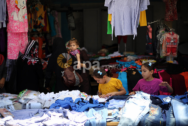 Riham and Hanin Zidan, 8-year-old, a Palestinian twins help their father as he sells clothes at a street market in al-Shati refugee camp, western Gaza City, Aug 12, 2013. The mother of Riham and Hanin faced a hard time conceiving a baby for a 15 years of marriage before they are born naturaly. Photo by Mahmoud Hamda