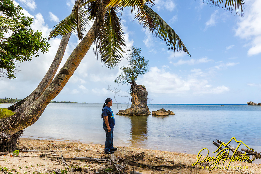 Peter Llamelo Rioja on on a beach in Guam taking in the scenery of a beautiful cove.