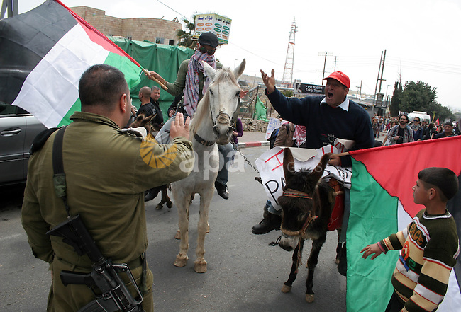 A Palestinian man and an international activist ride a donkey and a horse during a protest at a checkpoint in the West Bank town of Bethlehem March 28, 2010. Israeli border police clashed on Sunday with dozens of Palestinian Christians and Israeli activists who marched towards the checkpoint between Bethlehem and Jerusalem in protest against the separation barrier and demanded to be allowed into Jerusalem for Palm Sunday events. Photo by Najeh Hashlamoun