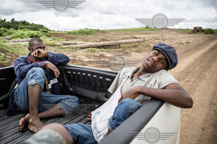 Men travelling in a pickup truck along a road built by a logging company.