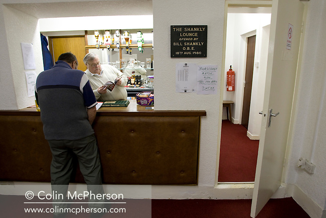 The barman reading the match programme in the Shankley Loungeprior to the Blue Square North fixture between hosts Workington AFC (red) and Boston United at Borough Park. The visitors won with a solitary sixth-minute goal by Jon Rowan in front of 388 spectators. Both Workington AFC and Boston United were members of the Football League, the Cumbrians losing League status in 1977 while the Lincolnshire club were relegated in 2007 and demoted two divisions for financial irregularities..
