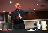 Dr. Anthony Fauci, director of the National Institute for Allergy and Infectious Diseases, cleans his hands as he prepares to testify before the Senate Health, Education, Labor and Pensions (HELP) Committee on Capitol Hill in Washington DC on Tuesday, June 30, 2020.  Fauci and other government health officials updated the Senate on how to safely get back to school and the workplace during the COVID-19 pandemic. <br /> Credit: Kevin Dietsch / Pool via CNP /MediaPunch
