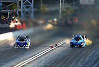 Mar 28, 2014; Las Vegas, NV, USA; NHRA funny car driver Robert Hight (left) races alongside Jeff Diehl during qualifying for the Summitracing.com Nationals at The Strip at Las Vegas Motor Speedway. Mandatory Credit: Mark J. Rebilas-