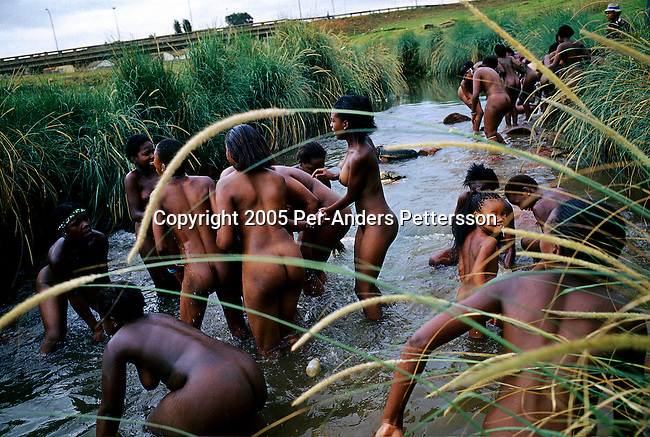 SOWETO, SOUTH AFRICA MARCH 11: Zulu maidens wash themselves in a river on March 11, 2005 in Soweto, Johannesburg, South Africa. About fifty girls celebrated their virginity by marching trough the streets of the township. Soweto is South Africa?s largest township and it was founded about one hundred years to make housing available for black people south west of downtown Johannesburg. The estimated population is between 2-3 million. Many key events during the Apartheid struggle unfolded here, and the most known is the student uprisings in June 1976, where thousands of students took to the streets to protest after being forced to study the Afrikaans language at school. Soweto today is a mix of old housing and newly constructed townhouses. A new hungry black middle-class is growing steadily. Most residents work in Johannesburg but the last years many shopping malls has been built, and people are starting to spend their money in Soweto.  .(Photo by Per-Anders Pettersson/Getty Images).