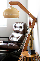 Modern leather armchair and wooden lamp