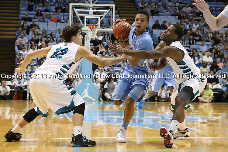 31 December 2013: North Carolina's Nate Britt (center) is defended by UNC Wilmington's Tanner Milson (12) and Chris Dixon (right). The University of North Carolina Tar Heels played the UNC Wilmington Seahawks at the Dean E. Smith Center in Chapel Hill, North Carolina in a 2013-14 NCAA Division I Men's Basketball game. UNC won the game 84-51.