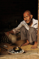 Man fanning the coal fire in order to heat butter for the lamps to be lit in worship rituals. Kathmandu, Nepal