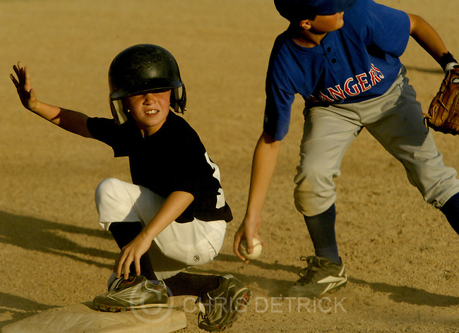 Centerville, UT--24 Jun 2005--.**Close Up**.Rockies Devin Porschatis, 10, slides safely into third base past the Ranger's Ryan Dudley, 12..The Rockies defeated the Rangers 7-4 in the 11-12 year old .Davis County Little League world series qualifying game Friday evening.  .Chris Detrick /Salt Lake Tribune.File #Little League CD05