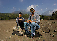 Diego Elias Mendoza Santos (left), 12, also known as Rambo, and Jorge Mario Gerónimo Lopez sit at the spot of Rambo's former home in an area of Panabaj, Guatemala on Tuesday, March 20, 2007. A deadly mudslide here was spawned by rains associated with Hurricane Stan in October 2005. Initially, up to 500 Tzujutil Maya villagers were believed to have been killed by the mudslide, which essentially  wiped away the town. Rambo lost his parents and a sister and brother. Mario escaped with his family. Forensic anthropologists from the Fundación de Antropología Forense de Guatemala have been working to unearth the bodies of the missing and have recovered more than 100. They have also found the number of missing to be lower than originally thought, after many people were located in shelters or living in other towns after the disaster.