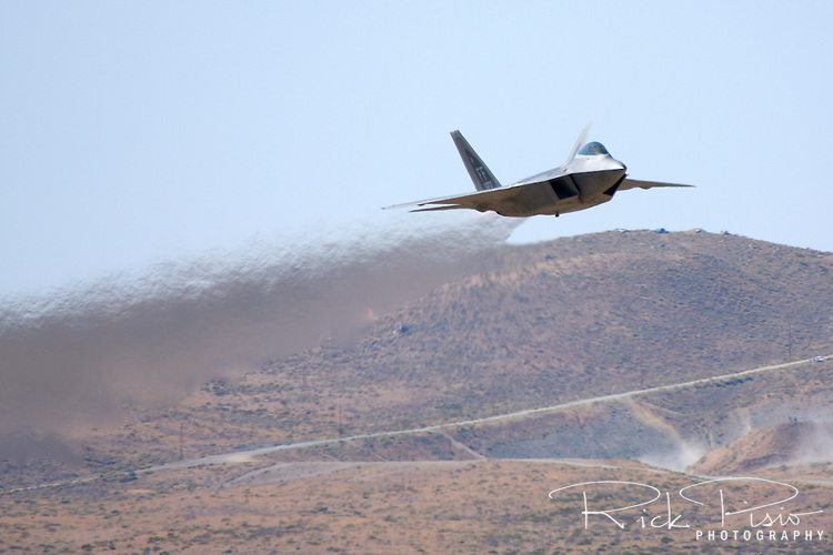 "United States Air Force pilot  Major Paul ""Max"" Moga, flying the F-22 Raptor, brings the heat while making a pass down the crowd as part of an airpower demonstration during the 2008 Reno National Championship Air Races at Stead Field in Nevada."